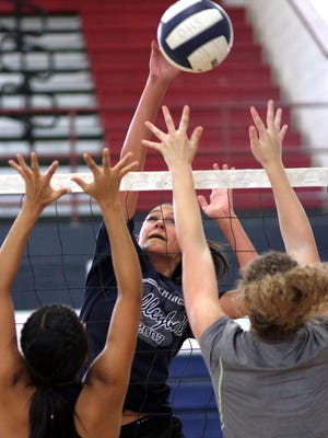 Sophomore middle blocker/hitter Vanessa Garcia attempts to hit over the Lady Cat block during Monday's after-school practice. The Deming Lady Cat volleyball team will be in Las Cruces Saturday for a preseason scrimmage.