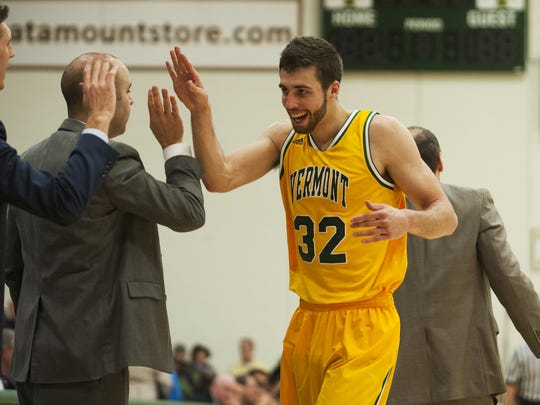 Catamounts forward Ethan O'Day (32) is congratulated