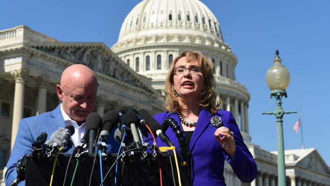Former congresswoman Gabrielle Giffords, standing with her husband, Mark Kelly, speaks on Capitol Hill on Oct. 2, 2017, about the mass shooting in Las Vegas.