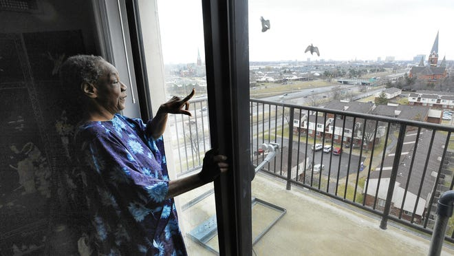 Fayette Coleman, who is a little nervous about heights, in her new home, an apartment near the medical center area overlooking Detroit, in Detroit, Michigan on March 9, 2016.