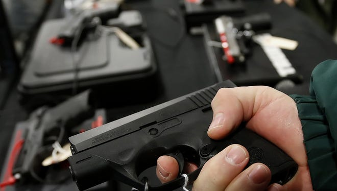 A man holds a Beretta U.S.A. Corp. handgun for sale at the Rocky Mountain Gun Show in Sandy, Utah, U.S., on Saturday, Jan. 5, 2013. A working group led by Vice President Joe Biden is seriously considering measures that would require universal background checks for firearm buyers, track the movement and sale of weapons through a national database, strengthen mental health checks and stiffen penalties for carrying guns near schools or giving them to minors. Photographer: George Frey/Bloomberg ORG XMIT: 159230386 [Via MerlinFTP Drop]
