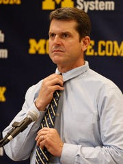 Michigan football coach Jim Harbaugh adjusts his tie while listening to a question during a news conference Feb. 4, 2015, in Ann Arbor.