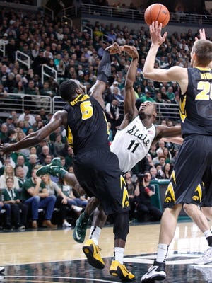 Michigan State's Lourawls Nairn Jr. draws the foul during an attempted layup against Iowa's Anthony Clemmons, left, and Jarrod Uthoff during the 1st half of MSU's 76-59 loss to Iowa Thursday at the Breslin Center.