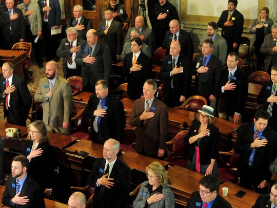 Legislators stand for the national anthem before Tuesday's