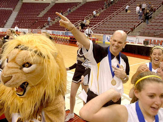 Red Lion basketball coach Don Dimoff finishes 'jamming' with his team, the Lions mascot and the cheerleaders after winning a District 3 championship.