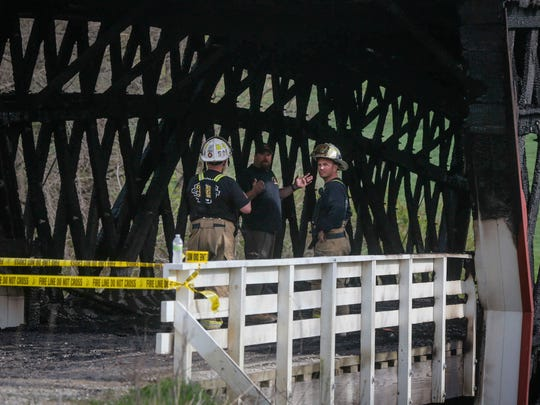 Madison County officials investigate a fire that destroyed the structure of the Cedar Covered Bridge, north of Winterset, Iowa, on Saturday, April 15, 2017. The fire was reported around 6 a.m., and was fully engulfed when fire crews arrived.