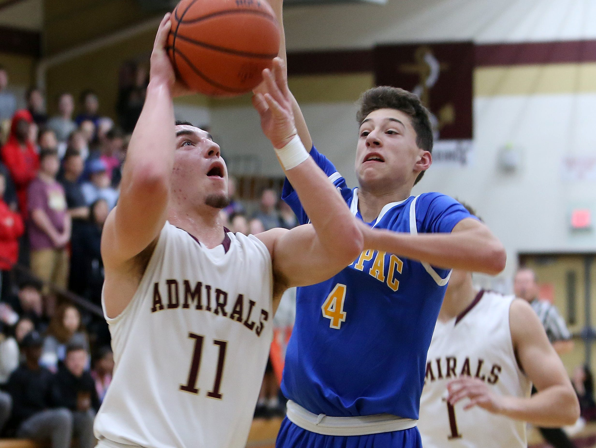 Arlington's Zach Dingee (11) goes up for a shot in front of Mahopac's Zack Puckhaber (4) during a boys basketball game at Arlington High School Jan. 12, 2017.