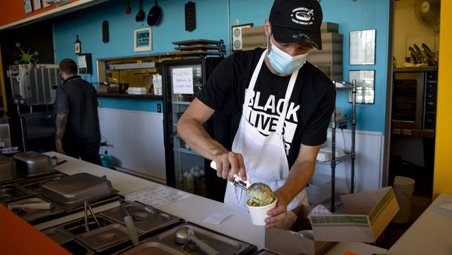 Mitch Werth prepares a to-go order at Cornbread Cafe. Owner Sheree Walters has printed shirts she and her employees wear in support of Black Lives Matter. [Andy Nelson/The Register-Guard] - registerguard.com