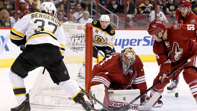 Bruins' Patrice Bergeron (37) scores a goal against Coyotes' Mike Smith, third from the left, as Coyotes' Derek Morris (53) defends and Coyotes' Keith Yandle, back right, and Bruins' Brad Marchand (63) look on during the first period of an NHL hockey game on Saturday, March 22, 2014.
