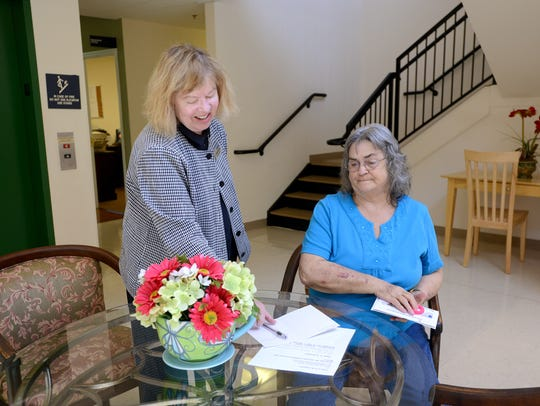 Linda Brown, left, places a get-well card on the table