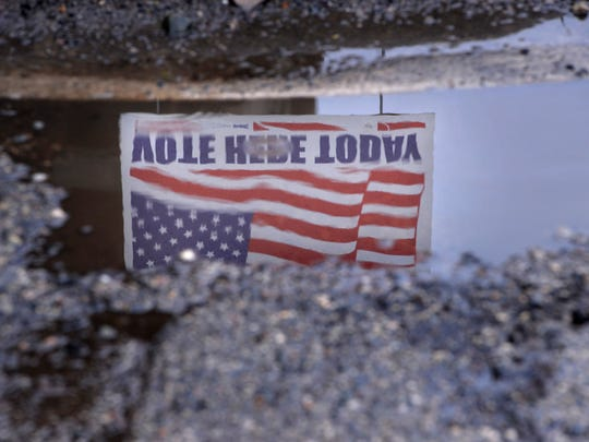 A voting sign is reflected in a rain-filled road pothole