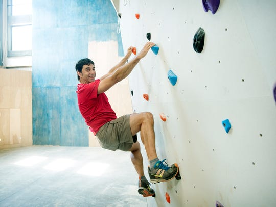 Stuart Cowles poses on the rock climbing wall inside