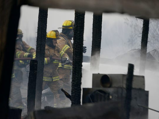 Firefighters spray what is left of a structure from a fire off of Ivy Hill Road.