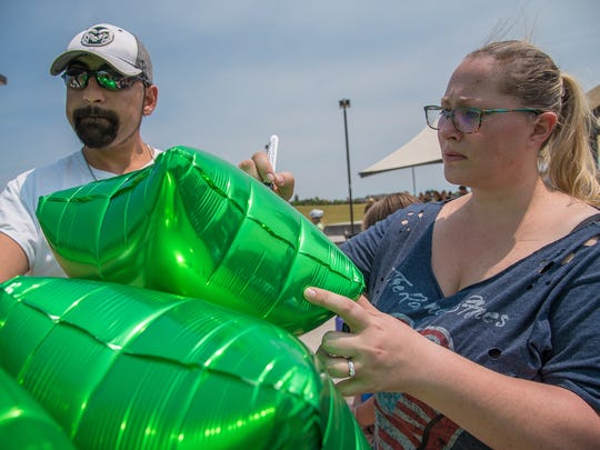 Christina Comeau of Loveland pens the hashtag #Gavinssidewalk on a balloon before releasing it at a memorial service for 13-year-old Gavin Myers on July 2 at Mehaffey Park in Loveland.