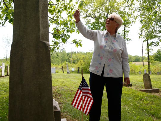 Norma Kahl inspects the gravestone of one her ancestors at the Wolford Cemetery on Friday afternoon.