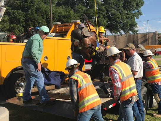 Sculptor Vic Payne works with crews from the City of