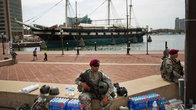 Members of the National Guard sit along the Inner Harbor in the aftermath of rioting following Monday's funeral for Freddie Gray, who died in police custody, Thursday, April 30, 2015, in Baltimore. New Jersey State Police troopers were also sent to Baltimore to help keep the peace in the city, and the troopers' deployment has now been extended through Tuesday, May 5.