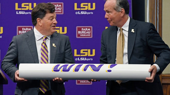 LSU president F. King Alexander, right, and Scott Woodward, left, hoist the 'WIN!' bar after Woodward was introduced as the new Director of Athletics for LSU, Tuesday April 23, 2019, in Baton Rouge, La. Woodward, who graduated from LSU in 1985, was the Vice-Chancellor of External Affairs at his alma mater under former Chancellor Mark Emmert from 2000-2004. Woodward spent time at Washington and Texas A&M before accepting the job at LSU as a replacement for Joe Alleva. (Bill Feig/The Advocate via AP)