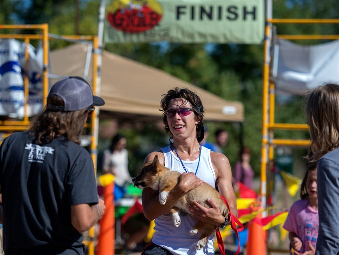 Nick Davis holds his corgi puppy Pickles as he finishes first in the Blue Sky Trail Marathon between Horsetooth Mountain Park and Devil's Backbone Open Space Sunday, Oct. 5, 2014. The marathon involves about 3500 feet of vertical gain, the majority of running done on single track trail, with terrain ranging from smooth dirt paths to very technical rocky sections.