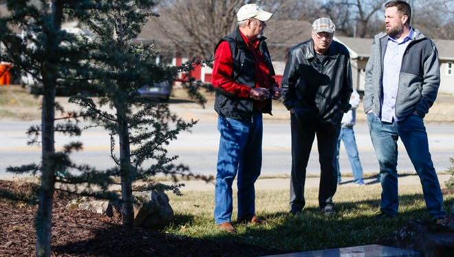 Gary Reece (left) talks with developers Sam E. Coryell (middle) and Sam M. Coryell (right) at the memorial to Reece's son, Allan M. Reece, in front of the Falcon apartment complex on South Ingram Mill Road.
