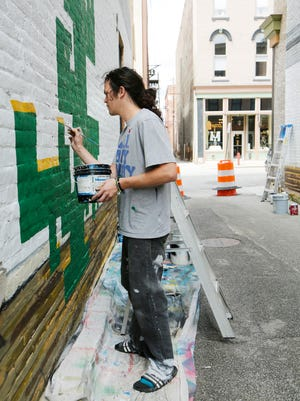 Local artist Brock Richert works on his creation for Alleypalooza Tuesday, May 10, 2016, in the alley behind the Knickerbocker in downtown Lafayette.