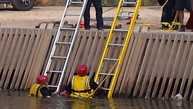 Phoenix police and fire officials try to help a man in the water along the Grand Canal after the man fell in the water and got his foot stuck in a grate.