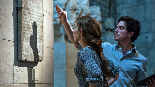 Scarlett (Perdita Weeks) and George (Ben Feldman) attempt to decipher ancient text in the twisting catacombs beneath the streets of Paris in 'As Above/So Below.'