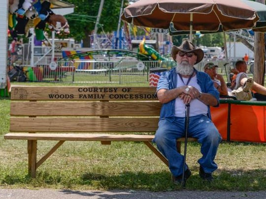 George Weaver of Liberty Township sits on a bench to rest during a past Butler County Fair after watching his grandson compete in the Market Hogs competition. The week-long event at the Butler County Fairgrounds is July 21-27 this year.