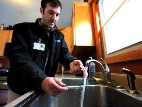 Cory Amos of A-TEC Energy, a contractor for MidAmerican Energy on HomeCheck audits, tests the water temperature at Mark and Jackie Wellman's home recently. He found it was a little hot, so he turned it down.
