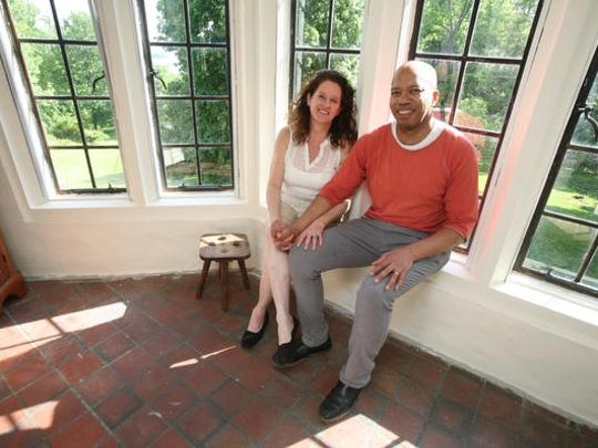 Homeowners Pattie McCluskey and Jim Moorhead in the sleeping porch of their 8,000-square foot house for sale in Croton-on-Hudson, has 36 rooms, 12 bedrooms, 13 bathrooms and 9 fireplaces on 19 acres.