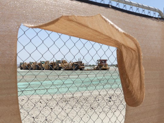 Construction graders sit idle at the Millineum Palm Desert construction site where chemical suppresant has been applied to the ground to control dust, August 28, 2015.