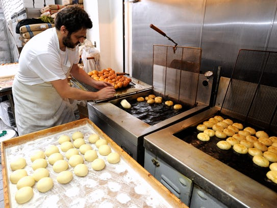 Michael Mitreski, of Shelby Township drops paczki into