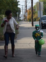 MJ Patterson and his mom Eboney walk down the street in pursuit of candy. Local businesses were open for trick or treating from 3-6 in Downtown Morganfield.