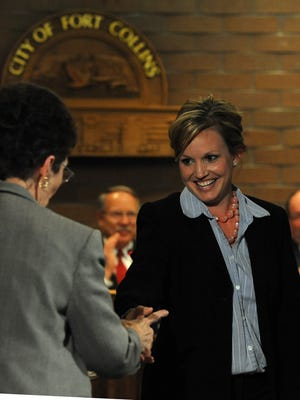 Aislinn Kottwitz, center, shakes hands with the Fort Collins city clerk after being sworn in to serve on the city council in this 2009 file photo.
