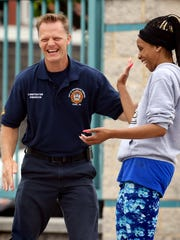 York City firefighter Erik Swanson jokes with Lincoln Charter School fifth-grade teacher Sakeenah Sweeney after advancing to third base during the Community Kickball game at the school Tuesday, May 29, 2018. The contest was part of a week-long series of fundraisers to benefit the American Cancer Society. All players--parents, teachers, emergency responders and students--paid a $5 fee to play in the game which pitted the adults against the school's fifth graders. Bill Kalina photo