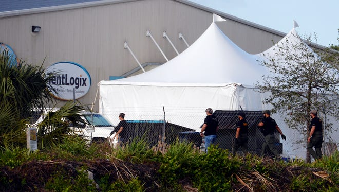 Federal law enforcement officials walk the perimeter of TentLogix, a tent rental business west of U.S. 1 in Fort Pierce, on Wednesday, March 28, 2018, as they conduct a criminal search warrant. About 28 people were taken into custody to be interviewed further according to Nestor Yglesias, spokesman for Homeland Security Investigations. To see more photos, visit TCPalm.com
