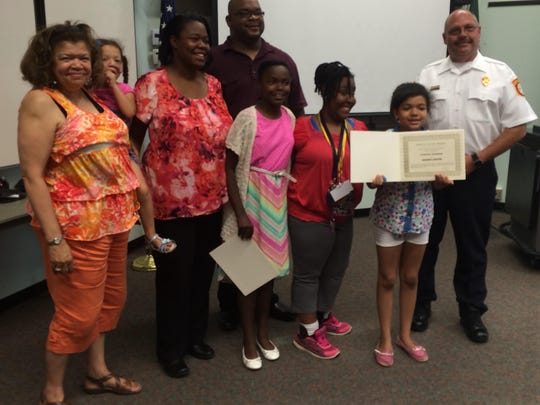 Family members pose with Danielle McKay, Grace Thomas, Annisha Carter and Fire Chief Jon Unruh.