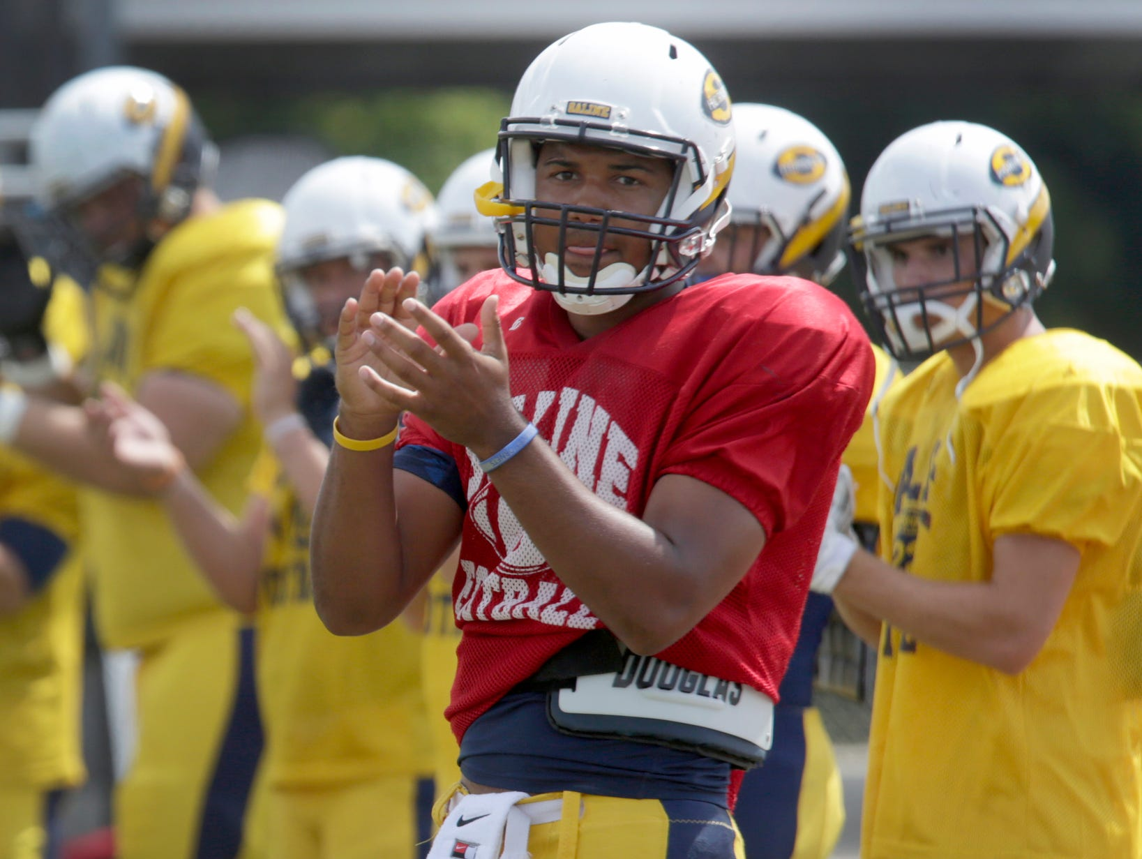 Saline quarterback Josh Jackson warms up on the field before a scrimmage against Dearborn on Aug. 20.