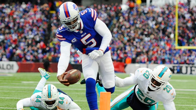 Buffalo Bills quarterback Tyrod Taylor (5) rushes past Miami Dolphins' Stephone Anthony (44) and Reshad Jones (20) for a touchdown during the first half of an NFL football game Sunday, Dec. 17, 2017, in Orchard Park, N.Y. (AP Photo/Adrian Kraus)