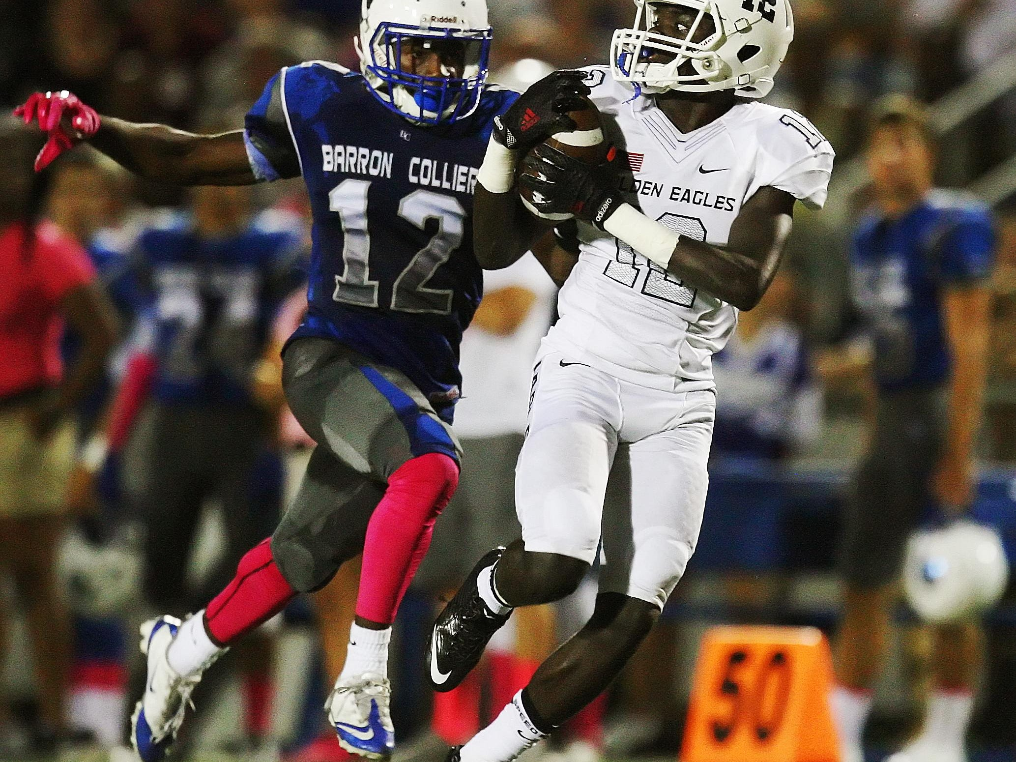 Naples High School's Woody Theork catches a pass against Barron Collier's Dana Brown on Friday at Barron Collier High School in Naples.