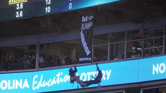 Two people hang from a banner they unfurled from the upper deck of Bank of America stadium in the second half of an NFL football game between the Carolina Panthers and the Indianapolis Colts in Charlotte, N.C., Monday, Nov. 2, 2015. (AP Photo/Mike McCarn)