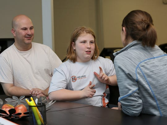 Katherine Phinney, 9, center, shares her daily eating routine with exercise physiologist Missy Sachs as her dad, Devin Phinney, left, looks on during a prime class at the Louisville Youth Training Center. Katherine has been able to halt excessive weight gain with the classes. Mar. 22, 2016