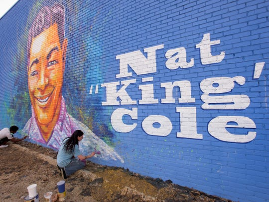 Artists Sunny Paulk and Corey Spearman paint a mural of Nat King Cole on the side of a building in downtown Montgomery, Ala.