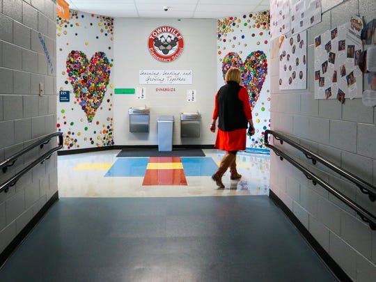 """Denise Fredericks, principal of Townville Elementary School, walks by student artwork called """"Work of Heart"""" on Thursday at the school. Students painted wood slices and pieced them together to create the display."""