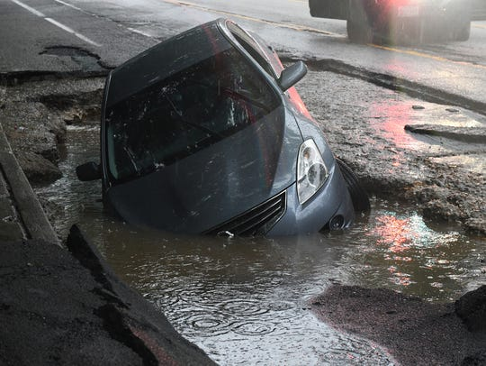 A car is seen in a sinkhole on Frederick Avenue near