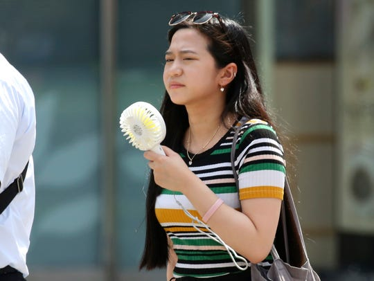 A woman holds a portable fan at a business district