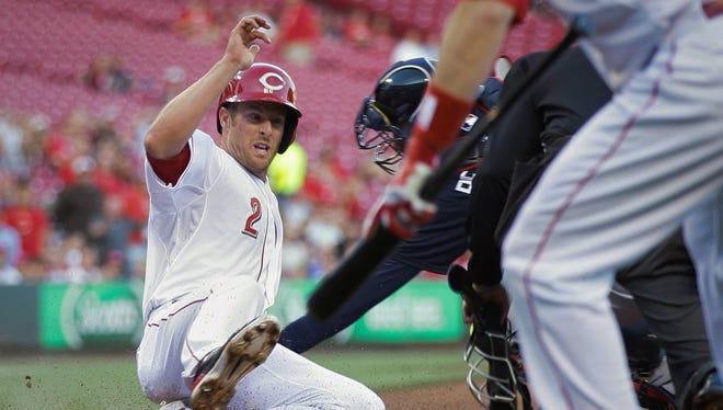 Cincinnati Reds' Zack Cozart (2) slides home safely as Atlanta Braves catcher Christian Bethancourt tries to make the tag.