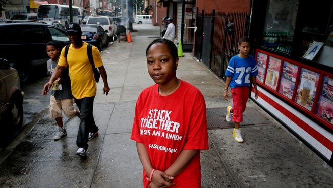 Shantel Walker stands for a photo outside a Brooklyn fast food restaurant, Thursday, June 19, 2014, in New York. Walker, who makes $8.25 per hour at a Brooklyn pizzeria will benefit if lawmakers are successful in raising the minimum wage within city borders. But efforts are running into opposition from state lawmakers from both parties and business groups who say a patchwork of minimum wages could lead to a confusing and unequal business climate in which labor costs would vary dramatically from city to city. (AP Photo/Julie Jacobson)