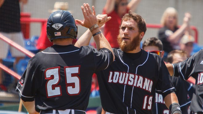 UL second baseman Jace Conrad (19) gives a high-five to teammate Kyle Clement after Clement scored a run in the fifth inning in a Sun Belt Conference tournament game against ULM.