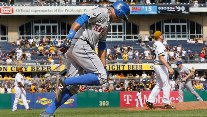 The Mets' Curtis Granderson, center, drops his bat and heads to first as Pittsburgh relief pitcher Mark Melancon, right, follows the ball that gets caught for the last out of the game on Sunday.